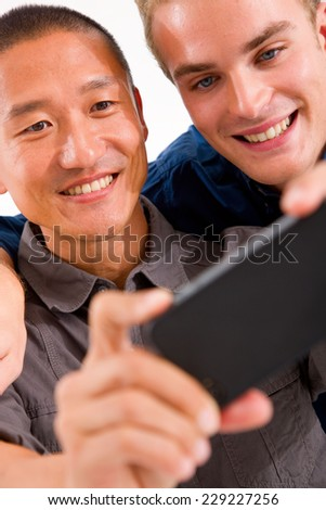 Close-up of two smiling friends taking self portrait with cell phone - stock photo