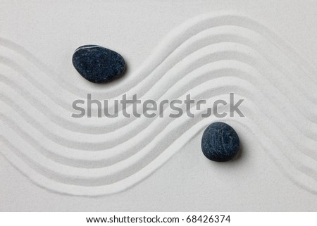 Close-up of two stones on white raked sand in a Japanese ornamental or zen garden.
