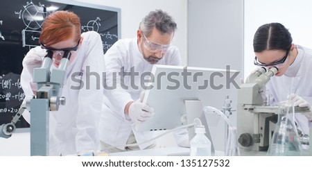 close-up of two students in a chemistry lab analyzing under microscope around lab tools and colorful liquids while the teacher is looking on a pc monitor - stock photo
