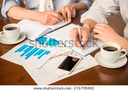 Close-up of  two successful businessmen sitting in urban cafe and making notes for project. - stock photo