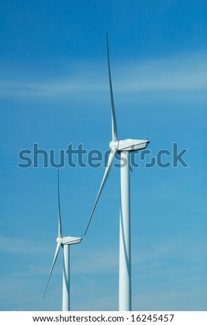 Close up of two windturbines on blue sky in France
