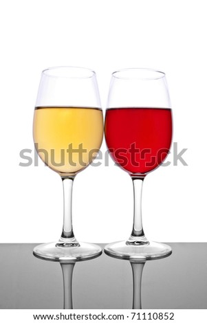 Close-up of two wineglasses. Yellow and red