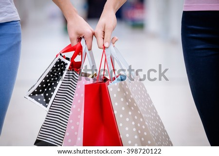Close-up of two women carrying shopping bags while shopping in mall