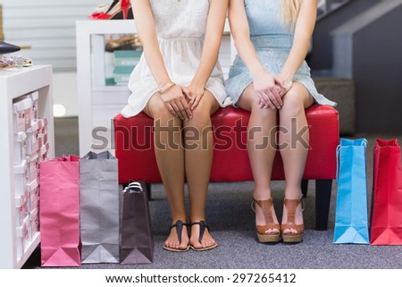 Close up of two women sitting with shopping bags in shoe store