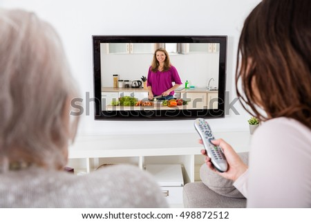 Close-up Of Two Women Watching Cooking Show On Television At Home