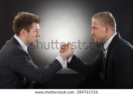 Close-up Of Two Young Businessman Competing In Arm Wrestling
