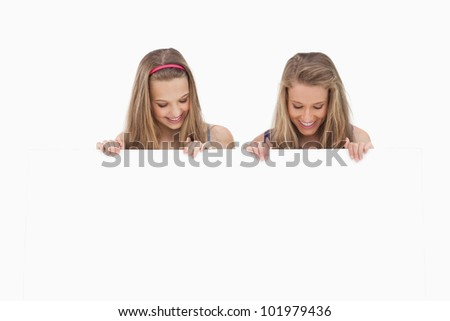 Close-up of two young women holding a blank board against white background - stock photo
