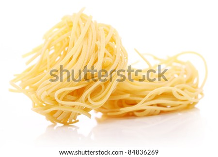 Close up of uncooked nest pasta against white background - stock photo