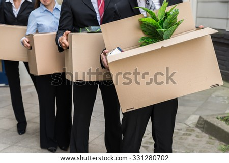 Close-up Of Unemployed Businesspeople Carrying Cardboard Boxes - stock photo