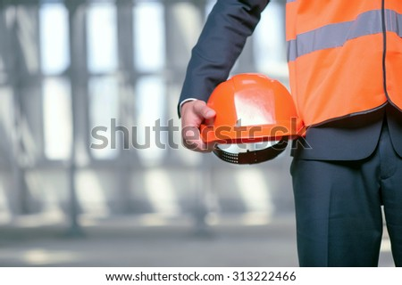 Close up of unrecognizable builder standing and holding an orange helmet in his hand. The man is wearing a workwear. Copy space in left side - stock photo