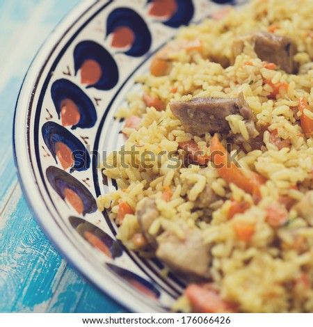 Close-up of uzbek traditional pilaf in a plate with ornaments