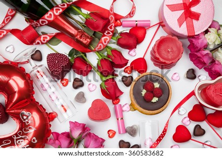 Close up of Valentine Day assortiment of different gifts, candies, red roses, cosmetics, candles, and bottle of Champagne. - stock photo