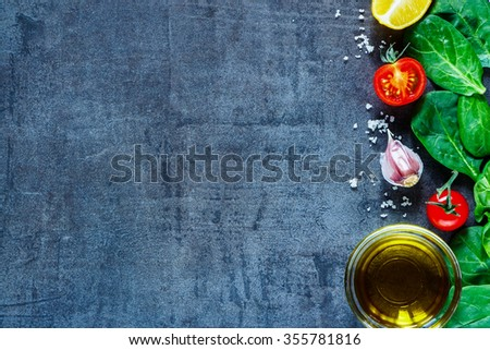 Close up of various vegetarian ingredients (spinach, tomatoes, olive oil, spices and herbs) on dark vintage table, top view. Healthy food, vegan or diet nutrition concept. Copy space. - stock photo