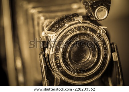 Close up of vintage camera showing lens and bellows with selective focus and sepia filter. - stock photo