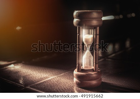 Close-up of vintage Hourglass on wood background vintage tone