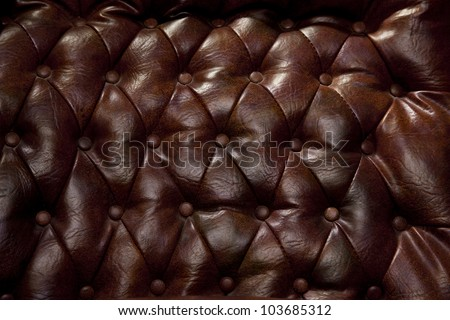 Close-up of vintage leather couch with seams and buttons. - stock photo