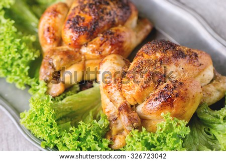 Close up of Vintage metal dish with two whole grilled chicken and green salad over white wooden table.  - stock photo