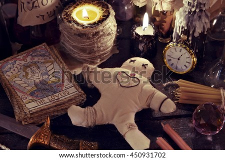 Close up of voodoo doll, ritual knife, burning candles, the tarot cards and magic objects. Halloween concept. There is no foreign text in the image, all symbols are imaginary and fantasy ones. - stock photo