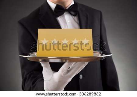 Close-up Of Waiter Serving Plate With Star Rating - stock photo