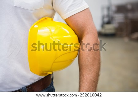 Close up of warehouse worker holding a hard hat in a large warehouse