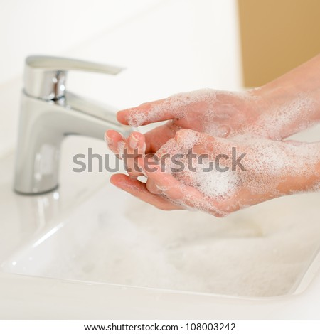 Close-up of washing hands with soap above bathroom sink - stock photo