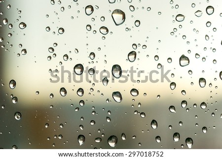 Close-up of water drops on the window with reflecting landscape. - stock photo