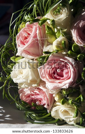 Close up of wedding bouquet of white and pink roses.