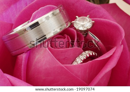Close-Up Of Wedding Rings And Engagement Ring In Red Rose