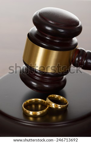 Close-up Of Wedding Rings And Wooden Gavel - stock photo