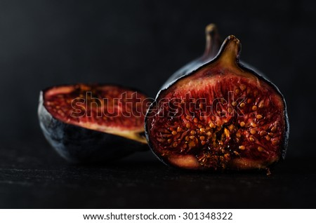 Close up of well ripened figs, cut open to expose seeds and juicy innards.  Still life composition on black slate with black background. - stock photo