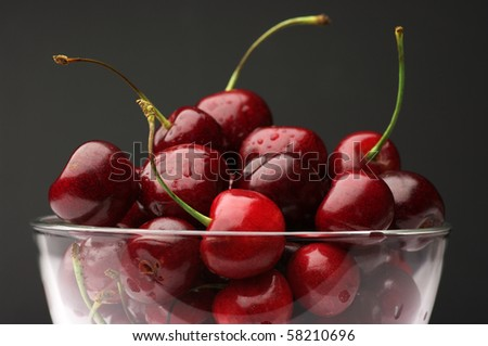Close-up of wet cherries in glass bowl on dark gray background. - stock photo