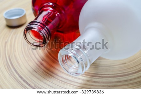 Close up of white and red glass bottle on bamboo plate,soft focus.
