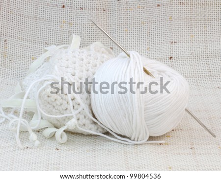 Close up of white ball (clew) of yarn and knitting hook