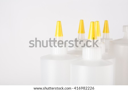 close up of white bottles with yellow caps on white background  - stock photo