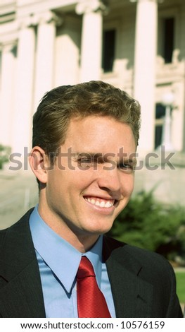 Close up of white businessman smiling in full suit and red tie in front of courthouse - stock photo