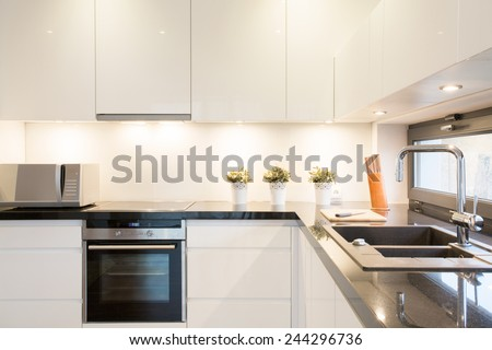 Close-up of white kitchen unit in modern interior - stock photo