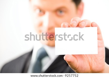 Close-up of white paper card in a businessman's hand on the background of his face