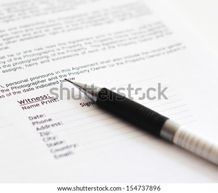 Close-up of white pen on contract