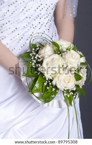 Close-up of white rose bouquet decorated with pearl beads in brides hands - stock photo