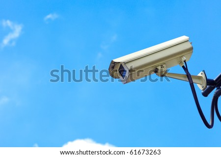 Close up of white security camera and white sky - stock photo