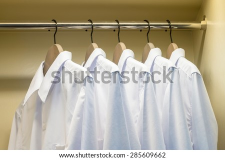 close up of white shirts hanging on coat hanger in wardrobe - stock photo