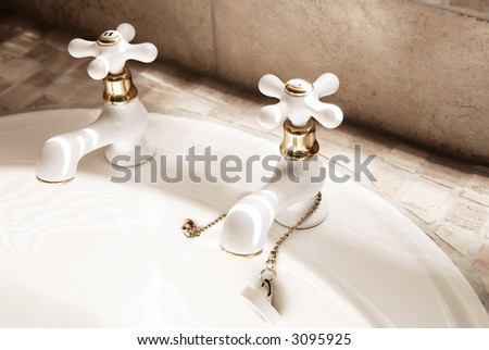 Close-up of white taps in the modern tiled bathroom. - stock photo