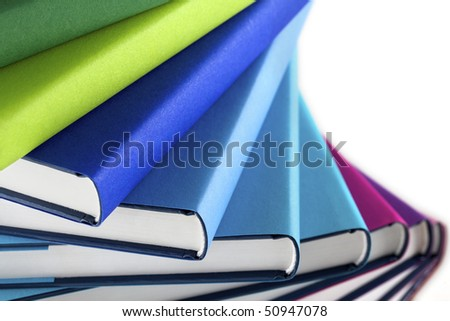 Close-up of winding stack of multi-colored real books on white background, side view. - stock photo