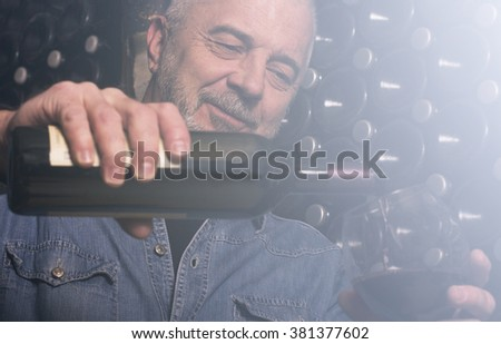 Close up of winemaker pouring wine to the glass in the wine cellar. Lens flare effect - stock photo