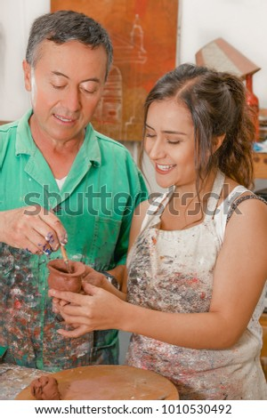 Close up of woman and man ceramist working together on sculpture on wooden table in workshop