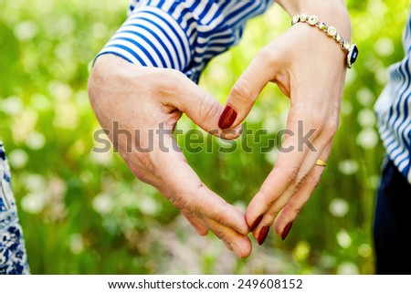 Close up of woman and man hands showing heart shape