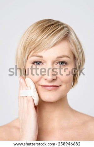 Close up of woman applying cosmetic powder on face - stock photo