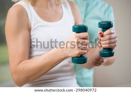 Close-up of woman at physiotherapist's cabinet holding dumbbells - stock photo