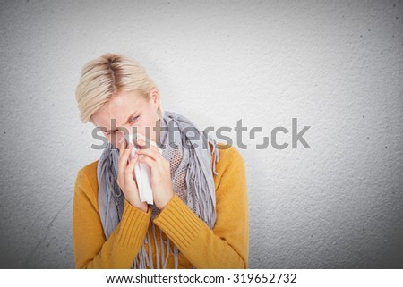 Close up of woman blowing her nose against grey wall - stock photo