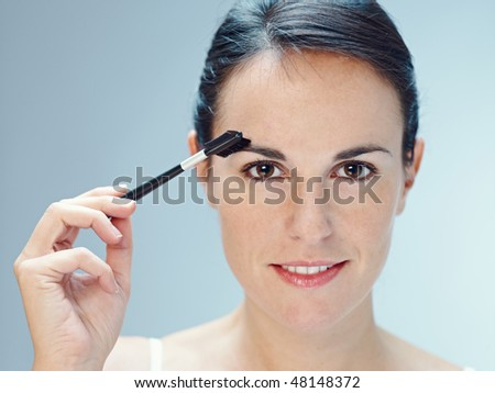 close up of woman brushing eyebrows with makeup brush. Copy space - stock photo